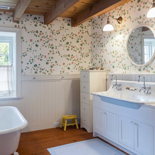 Example of a farmhouse master medium tone wood floor and brown floor claw-foot bathtub design in Philadelphia with shaker cabinets, white cabinets, multicolored walls, a trough sink, a hinged shower door and white countertops