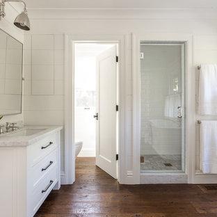 Modelo de cuarto de baño principal, de estilo de casa de campo, de tamaño medio, con lavabo bajoencimera, armarios estilo shaker, puertas de armario blancas, ducha empotrada, baldosas y/o azulejos blancos, baldosas y/o azulejos de cemento, paredes blancas y suelo de madera oscura