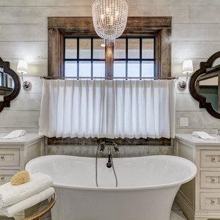 Diseño de cuarto de baño principal, campestre, con armarios con rebordes decorativos, puertas de armario beige, bañera exenta, paredes grises y lavabo bajoencimera