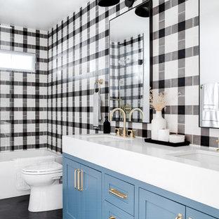 Foto de cuarto de baño campestre, de tamaño medio, con baldosas y/o azulejos blancas y negros, baldosas y/o azulejos de cerámica, encimeras blancas, armarios estilo shaker, puertas de armario azules, lavabo bajoencimera y suelo negro