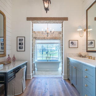 Example of a farmhouse medium tone wood floor and brown floor freestanding bathtub design in Austin with recessed-panel cabinets, blue cabinets, white walls, an undermount sink and white countertops