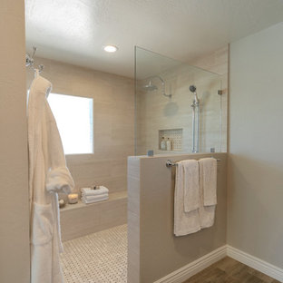 Inspiration for a mid-sized country master bathroom in Phoenix with raised-panel cabinets, black cabinets, a curbless shower, a two-piece toilet, beige tile, porcelain tile, grey walls, porcelain floors, an undermount sink, engineered quartz benchtops, brown floor, an open shower and white benchtops.