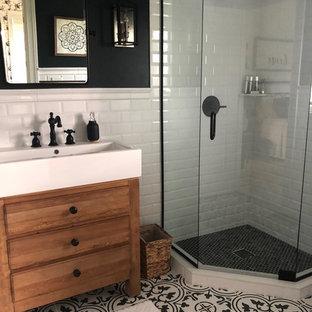 Foto på ett litet lantligt badrum, med möbel-liknande, skåp i ljust trä, en hörndusch, en toalettstol med hel cisternkåpa, vit kakel, keramikplattor, svarta väggar, klinkergolv i keramik, ett avlångt handfat, svart golv och dusch med gångjärnsdörr