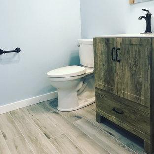 Foto di una piccola stanza da bagno country con ante con riquadro incassato, ante in legno scuro, WC a due pezzi, pareti blu, pavimento con piastrelle effetto legno, top in quarzo composito, pavimento grigio, top bianco, toilette, un lavabo e mobile bagno freestanding