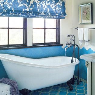 Diseño de cuarto de baño mediterráneo con bañera con patas, paredes multicolor, suelo de baldosas de terracota y suelo azul