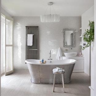 Bild på ett stort lantligt badrum, med ett fristående handfat, vita skåp, ett fristående badkar, porslinskakel, vita väggar, klinkergolv i porslin, vit kakel, skåp i shakerstil och beiget golv