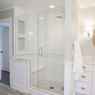 This is an example of a mid-sized country master bathroom in Chicago with an undermount sink, raised-panel cabinets, white cabinets, a corner shower, subway tile, green walls, porcelain floors and white tile.