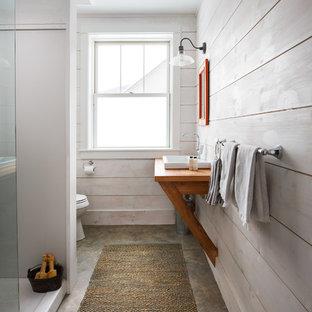Diseño de cuarto de baño campestre con ducha empotrada, paredes blancas, suelo de cemento, lavabo encastrado, encimera de madera, suelo marrón y encimeras marrones