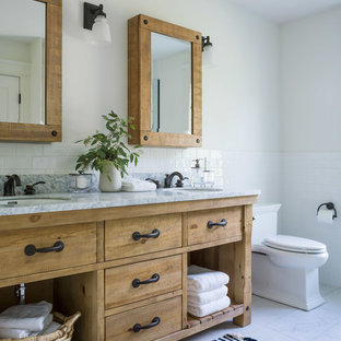 Inspiration for a mid-sized farmhouse master white tile and subway tile porcelain floor and white floor bathroom remodel in Other with medium tone wood cabinets, a two-piece toilet, white walls, an undermount sink, solid surface countertops, white countertops and furniture-like cabinets
