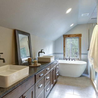 Cette image montre une petite salle de bain principale rustique avec un placard en trompe-l'oeil, des portes de placard marrons, une baignoire indépendante, une douche à l'italienne, un WC séparé, un carrelage gris, des carreaux de porcelaine, un mur gris, un sol en carrelage de céramique, une vasque, un plan de toilette en stéatite, un sol gris, une cabine de douche à porte battante et un plan de toilette vert.