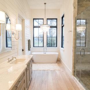 Foto di una stanza da bagno country con ante con riquadro incassato, ante grigie, vasca freestanding, doccia alcova, pareti bianche, lavabo sottopiano, pavimento beige e porta doccia a battente