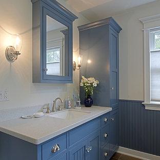 Idee per una stanza da bagno american style di medie dimensioni con ante in stile shaker, ante blu, vasca da incasso, pareti bianche, pavimento in ardesia, lavabo sottopiano e top in superficie solida