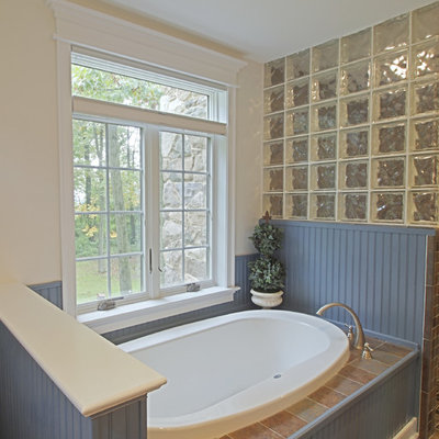 Inspiration for a mid-sized craftsman slate floor drop-in bathtub remodel in Philadelphia with shaker cabinets, blue cabinets, white walls, an undermount sink and solid surface countertops