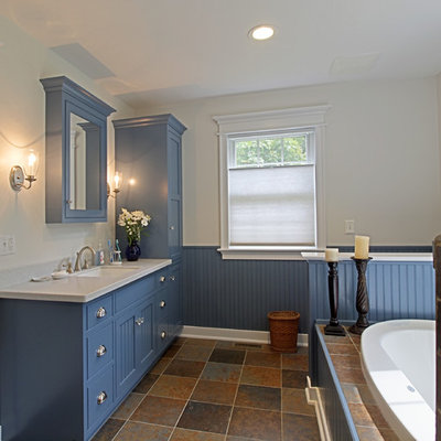 Example of a mid-sized arts and crafts slate floor drop-in bathtub design in Philadelphia with shaker cabinets, blue cabinets, white walls, an undermount sink and solid surface countertops