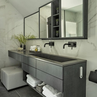 Example of a trendy gray tile and white tile gray floor, double-sink and vaulted ceiling bathroom design in London with flat-panel cabinets, gray cabinets, white walls, a trough sink, gray countertops and a floating vanity