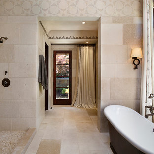 Immagine di una stanza da bagno mediterranea con vasca freestanding, doccia aperta, doccia aperta e piastrelle di pietra calcarea