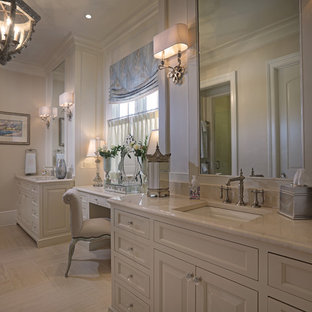 Large classic ensuite bathroom in Atlanta with raised-panel cabinets, white cabinets, a one-piece toilet, beige tiles, beige walls, vinyl flooring, a submerged sink and engineered stone worktops.