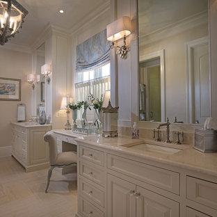 Modelo de cuarto de baño principal, tradicional, grande, con armarios con paneles con relieve, puertas de armario blancas, sanitario de una pieza, baldosas y/o azulejos beige, paredes beige, suelo vinílico, lavabo bajoencimera y encimera de cuarzo compacto
