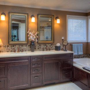 Bild på ett mellanstort vintage beige beige en-suite badrum, med luckor med infälld panel, skåp i mörkt trä, ett platsbyggt badkar, brun kakel, glaskakel, bruna väggar, ett undermonterad handfat, klinkergolv i porslin, bänkskiva i kvarts och beiget golv