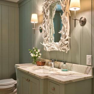 Esempio di una stanza da bagno con doccia stile marinaro di medie dimensioni con ante in stile shaker, ante verdi, WC a due pezzi, piastrelle beige, pareti verdi, lavabo sottopiano, top in superficie solida, pavimento in legno massello medio e pavimento marrone