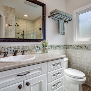 Alcove shower - mid-sized traditional 3/4 gray tile and subway tile alcove shower idea in Los Angeles with recessed-panel cabinets, white cabinets, white walls, a drop-in sink, a two-piece toilet, engineered quartz countertops, a hinged shower door and beige countertops