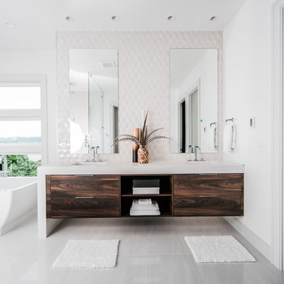 Freestanding bathtub - contemporary white tile gray floor freestanding bathtub idea in Seattle with flat-panel cabinets, dark wood cabinets, white walls, an undermount sink and white countertops