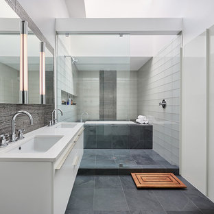Example of a trendy master gray tile, white tile and glass tile porcelain tile bathroom design in DC Metro with flat-panel cabinets, white cabinets, white walls, an undermount sink, solid surface countertops and an undermount tub