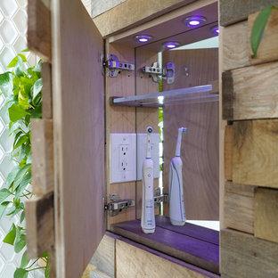 Minimalistisk inredning av ett stort vit vitt en-suite badrum, med släta luckor, blå skåp, ett fristående badkar, en kantlös dusch, en toalettstol med hel cisternkåpa, vit kakel, porslinskakel, blå väggar, klinkergolv i porslin, ett undermonterad handfat, bänkskiva i kvarts, grått golv och dusch med gångjärnsdörr