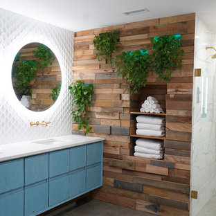 Bathroom - large scandinavian master white tile and porcelain tile porcelain floor and gray floor bathroom idea in Atlanta with flat-panel cabinets, blue cabinets, a one-piece toilet, blue walls, an undermount sink, engineered quartz countertops, a hinged shower door and white countertops