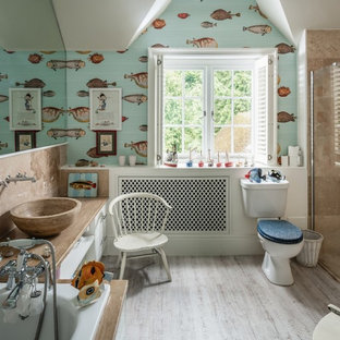 Example of a mid-sized eclectic beige floor drop-in bathtub design in Hampshire with a two-piece toilet, a vessel sink, white cabinets, multicolored walls and beige countertops