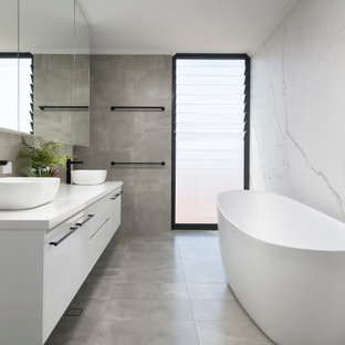 This is an example of a mid-sized contemporary master bathroom in Perth with flat-panel cabinets, white cabinets, a freestanding tub, gray tile, porcelain tile, pebble tile floors, a vessel sink, grey floor and white benchtops.
