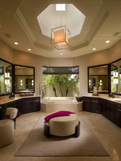 example of a trendy beige tile beige floor drop in bathtub design in miami with