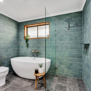 This is an example of a tropical bathroom in Adelaide with dark wood cabinets, a freestanding tub, a curbless shower, blue tile, green tile, grey floor, an open shower and white benchtops.