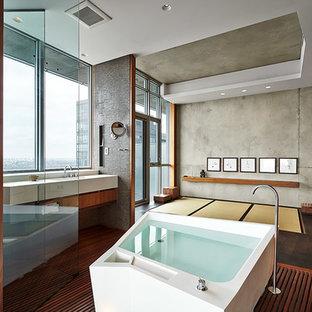 Idee per una stanza da bagno padronale etnica con ante lisce, ante in legno scuro, vasca giapponese, pareti grigie, pavimento in legno massello medio e pavimento marrone