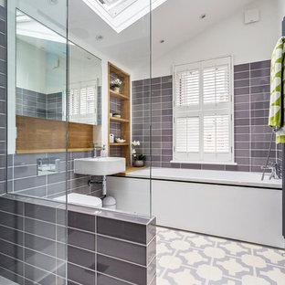 Ispirazione per una piccola stanza da bagno per bambini contemporanea con ante di vetro, vasca da incasso, doccia aperta, WC sospeso, piastrelle in ceramica, pareti bianche, pavimento in vinile, lavabo sospeso e pavimento multicolore