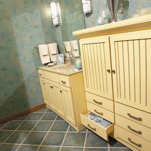 Idee per una stanza da bagno tradizionale di medie dimensioni con ante a persiana, ante gialle, pareti blu, pavimento con piastrelle in ceramica, lavabo integrato, top in superficie solida e pavimento blu