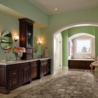 Imagen de cuarto de baño principal, tradicional, extra grande, con armarios con paneles con relieve, puertas de armario de madera en tonos medios, bañera empotrada, paredes verdes, lavabo bajoencimera y suelo beige