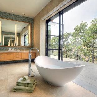 Foto på ett funkis badrum, med släta luckor, skåp i mellenmörkt trä, ett fristående badkar, blå kakel, mosaik och travertin golv