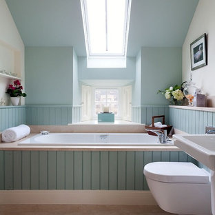 Example of a transitional stone tile limestone floor and beige floor drop-in bathtub design in Other with a wall-mount sink, a wall-mount toilet and blue walls