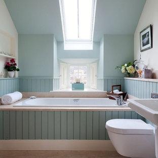 Ejemplo de cuarto de baño tradicional renovado con lavabo suspendido, bañera encastrada, sanitario de pared, paredes azules, baldosas y/o azulejos de piedra, suelo de piedra caliza y suelo beige