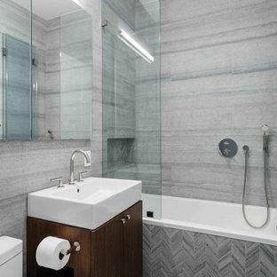 ニューヨークの中くらいのコンテンポラリースタイルのおしゃれな浴室 (フラットパネル扉のキャビネット、ドロップイン型浴槽、大理石タイル、大理石の床、大理石の洗面台、グレーの床、濃色木目調キャビネット、シャワー付き浴槽、一体型トイレ、グレーのタイル、コンソール型シンク、オープンシャワー、ニッチ、洗面台1つ、造り付け洗面台) の写真