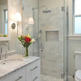 На фото: маленькая ванная комната в стиле современная классика с врезной раковиной, плоскими фасадами, белыми фасадами, угловым душем, мраморной столешницей, серой плиткой, каменной плиткой, белыми стенами и мраморным полом