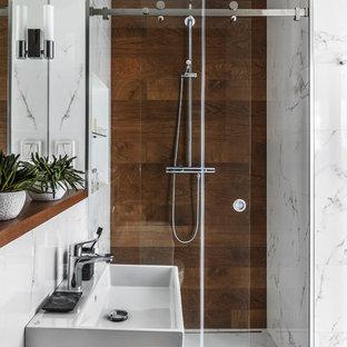 Idee per una stanza da bagno con doccia contemporanea con doccia alcova, piastrelle marroni, piastrelle bianche, lavabo sospeso, porta doccia scorrevole, pavimento in marmo e pavimento bianco