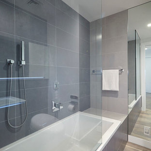 Bathroom - large contemporary master gray tile and porcelain tile medium tone wood floor and beige floor bathroom idea in New York with a one-piece toilet, flat-panel cabinets, white cabinets, white walls, an integrated sink and glass countertops