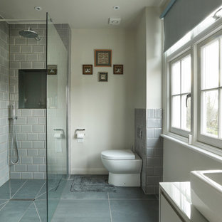 Medium sized contemporary wet room in London with flat-panel cabinets, white cabinets, a one-piece toilet, beige walls, a vessel sink, grey floors and an open shower.