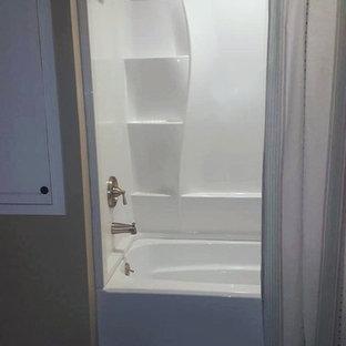 Modelo de cuarto de baño con ducha, de estilo de casa de campo, pequeño, con armarios con paneles lisos, puertas de armario blancas, bañera exenta, combinación de ducha y bañera, baldosas y/o azulejos marrones, suelo de linóleo, lavabo encastrado y encimera de granito