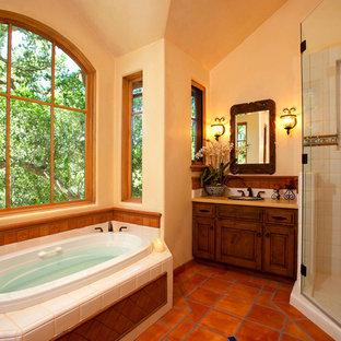 Ispirazione per una stanza da bagno mediterranea con vasca da incasso, doccia ad angolo e pavimento rosso