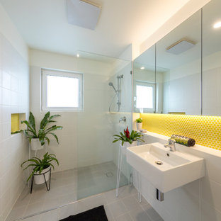 Photo of a small contemporary bathroom in Canberra - Queanbeyan with glass-front cabinets, a curbless shower, yellow tile, ceramic tile, white walls, cement tiles, a wall-mount sink, grey floor and an open shower.