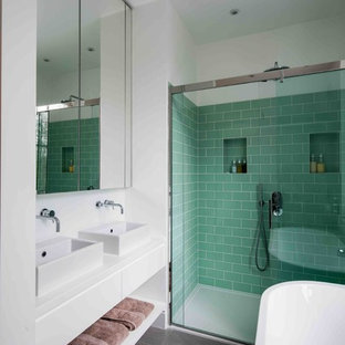 Medium sized contemporary bathroom in London with a freestanding bath, a walk-in shower, green tiles, metro tiles, white walls, a vessel sink, black floors and a sliding door.