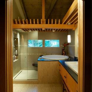 Ejemplo de cuarto de baño principal, asiático, de tamaño medio, con lavabo sobreencimera, armarios estilo shaker, puertas de armario de madera clara, encimera de granito, bañera japonesa, ducha abierta, sanitario de pared, baldosas y/o azulejos grises, baldosas y/o azulejos de porcelana, paredes beige y suelo de baldosas de porcelana